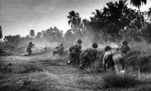 Dutch Marines during a shootout, covered by a natural elevation, Indonesia, 1946.